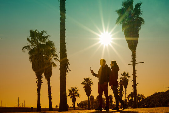 silhouette of young couple shooting together beautiful sunset with smart cell phone