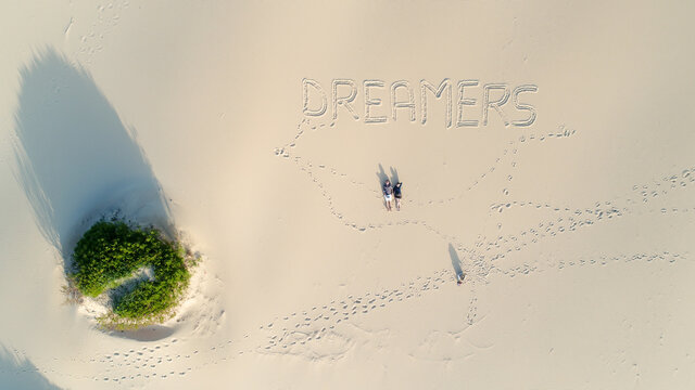 couple laying on beautiful white sand beach, dreamers written down on the sand, bird eye view