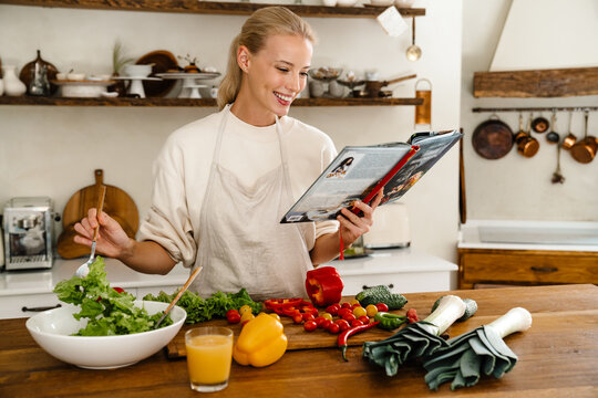 Beautiful joyful woman reading cookbook and smiling while making lunch