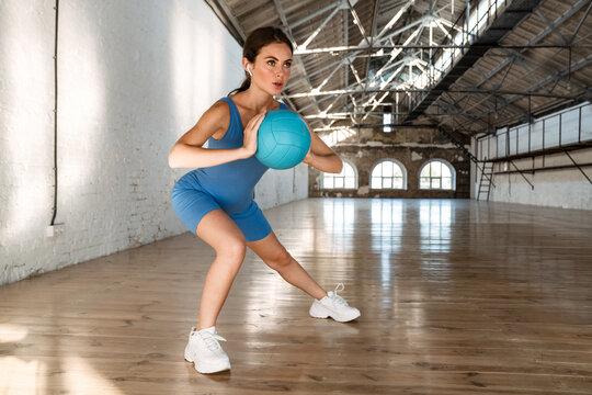 Beautiful brunette sportswoman in earphones working out with ball