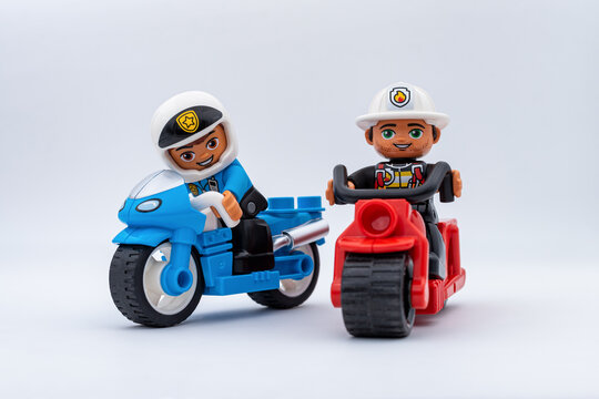 PARIS, FRANCE - NOVEMBER 17, 2020: packshot of two Lego minifigures representing motorbikers isolated on light grey background. A police officer on a blue motorbike followed by a fireman on a red one.