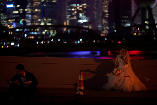 A couple takes a break during their wedding photo session on a street amid the global outbreak of the coronavirus disease (COVID-19) in Shanghai