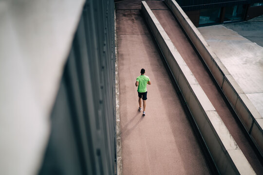Back top view of strength triathlete dressed in sportswear spending workout time for sprinting and speed running, unrecognizable male jogger doing cardio training for prepare to marathon race
