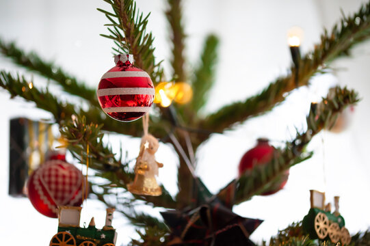 Decorated Christmas tree, real Nordmann fir in front of blurred background. Macro photography shows different pendants, angel, locomotive, gift, balls and light chain