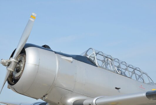 vintage military propeller airplane in silver colors, blue sky in the background