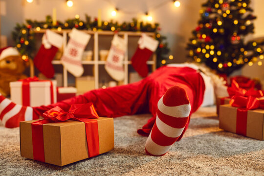 Gift box tied with red ribbon beside tired drunk Santa lying asleep on floor in living room