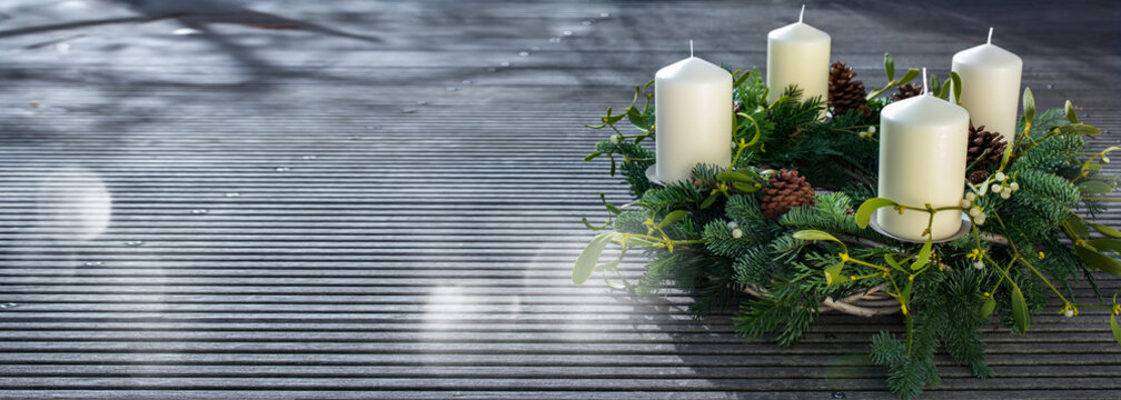 Advent wreath on gray wooden planks with silver bokeh lights. Horizontal christmas background with space for text.