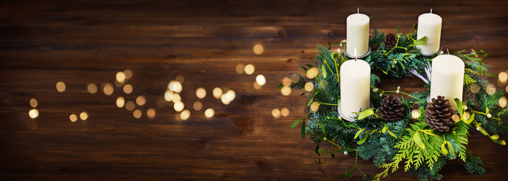 Advent wreath on dark wooden table with golden bokeh lights and christmas mood. Horizontal background with space for text