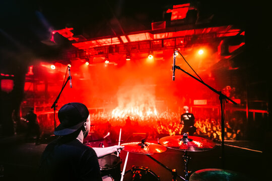 Band on stage. Drummer playing drum set at concert on stage. Music show. Bright scene lighting in club, drum sticks in hands. Fans burn red flares at a rock concert. View from the stage to the drummer