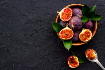 Fresh ripe figs in a bowl with leaves. Mediterranean fruit background