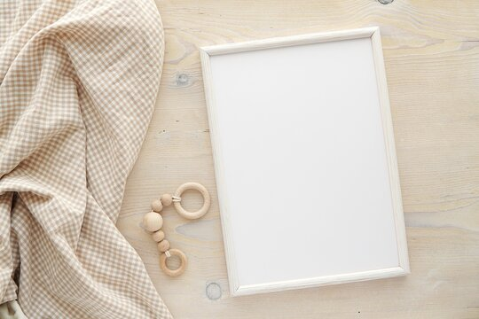 Nursery frame mockup, vertical white wooden frame mock up for baby room art, pregnancy announcement, top view, flat lay.