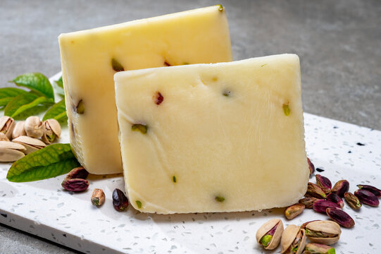 Cheese collection, fresh Italian pecorino cheese made from sheep milk filled with pistachio nuts from Bronte, Sicily