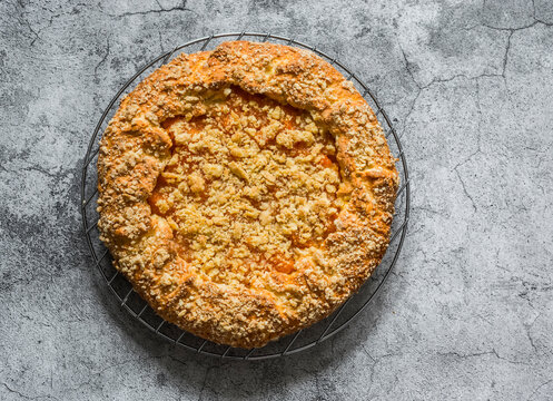 Caramelized pumpkin cinnamon crumble pie on a grey background, top view