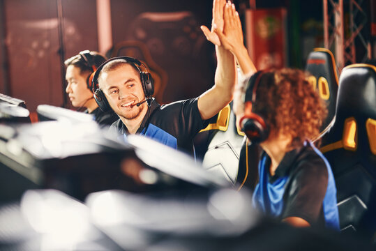 Winning. Two young happy professional cyber sport gamers giving high five to each other, celebrating success while participating in eSports tournament