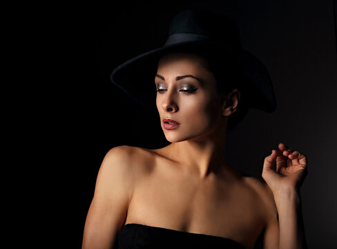 Beautiful makeup woman with elegant healthy neck, nude back and shoulder on black background in fashion hat with empty copy space. Closeup