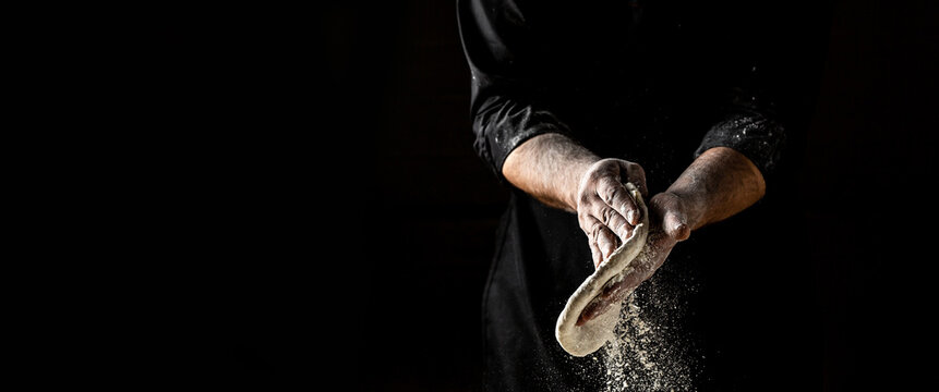Beautiful and strong men's hands knead the dough make bread, pasta or pizza. Powdery flour flying into air. chef hands with flour in a freeze motion of a cloud of flour midair