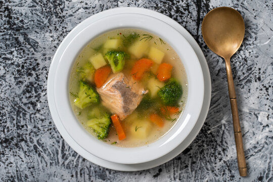 Fresh salmon fish soup with carrots, potatoes and onions in a white plate, close up. Top view