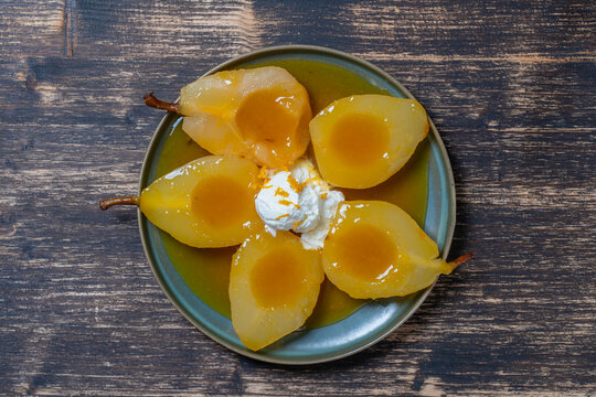 Baked pears in orange juice with ice cream, close up. Delicious dessert.