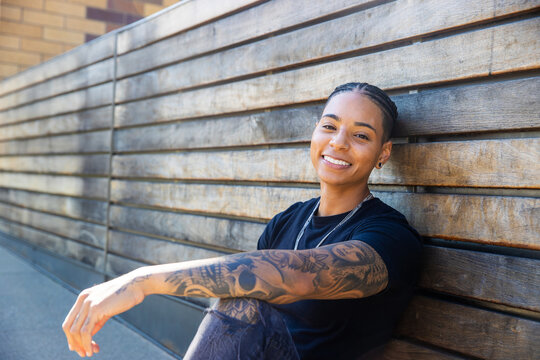 Young African American woman with tattoos on arm wearing black tee shirt sitting against wood wall outside