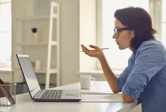 Woman sitting at home with laptop and discussing things online during conversation