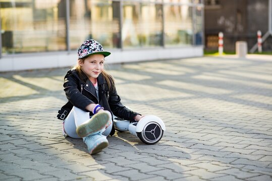 Young satisfied girl is resting sitting on a hoverboard somewhere in the city.