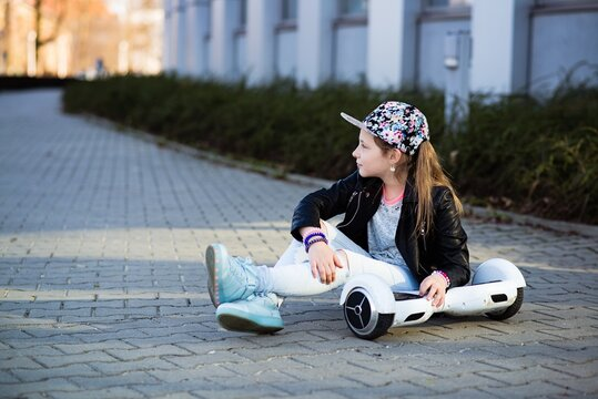 A 10-year-old girl in a flower cap sits with hers hoverboard.
