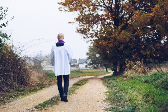 A christian priest is walking on a country road.