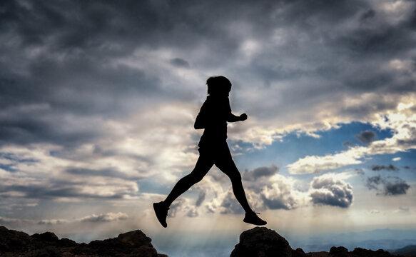 Frau springt über eine Klippe als Metapher für Veränderung und Motivation