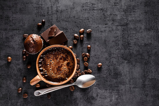 Freshly brewed espresso on a black stone table cup. Roasted arabica and robusta coffee beans.Coffee beans wallpaper.Top view, flat lay with copy space for your text.