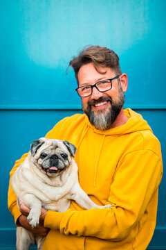 Best friend together forever concept with handsome cheerful adult man and his adorable puppy old pug dog portrait - people and animals love concept for happiness in life