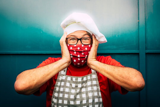 Scared and surprised adult man with red face protection mask for coronavirus - concept of restaurant owner worried for lockdown and outbreak for covid-19 and economy business crisis