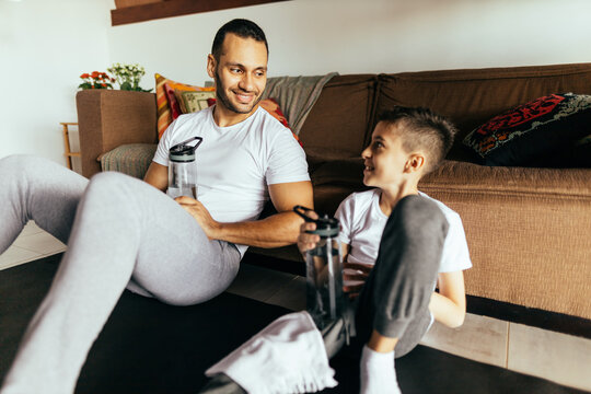Latin father and son rest after exercising at home