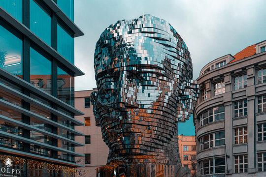 Close up of Head of Franz Kafka in Prague, Czech Republic. Sculpture reflects sunset lights. David Cherny artwork