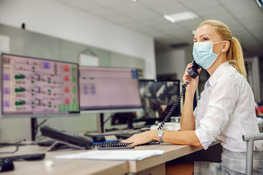 Dedicated hardworking blond female boss in suit with face mask on sitting in control room in heating plant and having important phone conversation during corona virus outbreak.