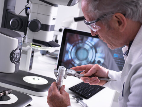Engineer using a dial calliper and a 3d stereo microscope for quality control in the manufacturing of engineering components for industry