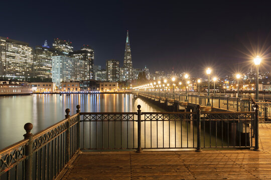 Pier 7 with illuminated building in background at San Francisco, California, USA