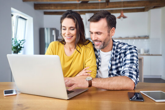 Couple sitting at dining table, using laptop, smiling