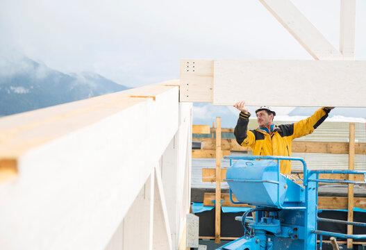 Austria, worker on hoist, positioning roof construction