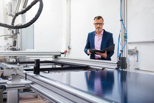 Mature businessman in solar factory holding folder