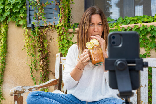 Female nutritionist drinking juice from jar while vlogging through smart phone at back yard