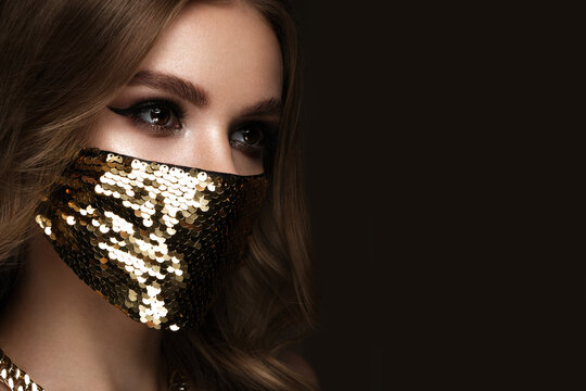 Portrait of a beautiful woman in a gold mask with sequins and classic makeup. Mask mode during the covid pandemic