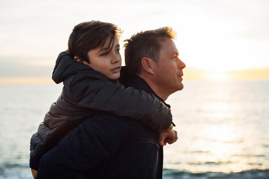Father carrying son piggyback by the sea
