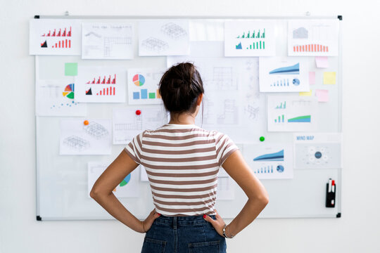 Young female architect with hands on hip examining charts on whiteboard at office