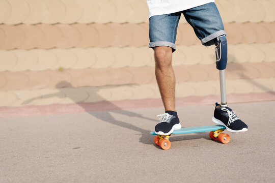 Young man with physical disability standing on skateboard at sports court