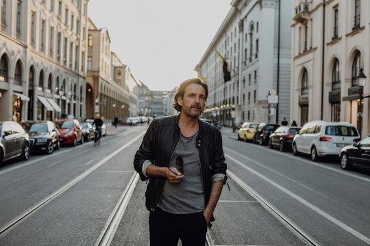 Man wearing leather jacket walking in the street, Munich, Germany