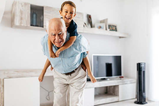 Portrait of grandfather giving his grandson a piggyback ride in the living room
