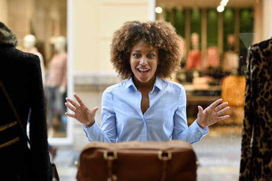 Excited woman with afro hairstyle looking in shop window