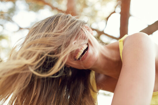 Portrait of laughing young woman with blowing hair