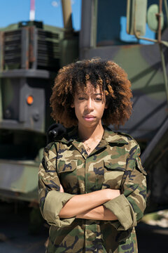 Confident young female army soldier with arms crossed standing against truck at military base