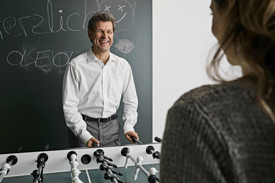 Businessman playing foosball with female colleague